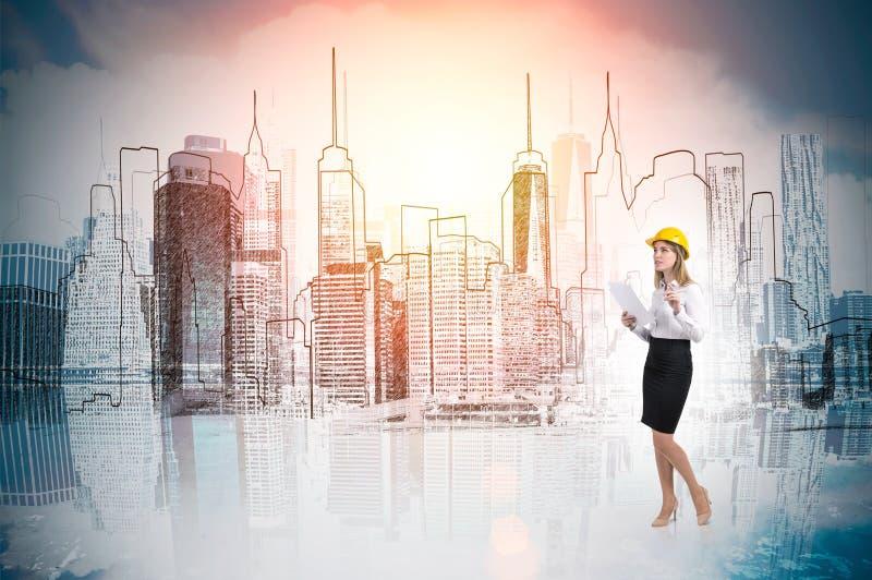 Kvinnan i gul hård hatt och cityscape skissar royaltyfria foton
