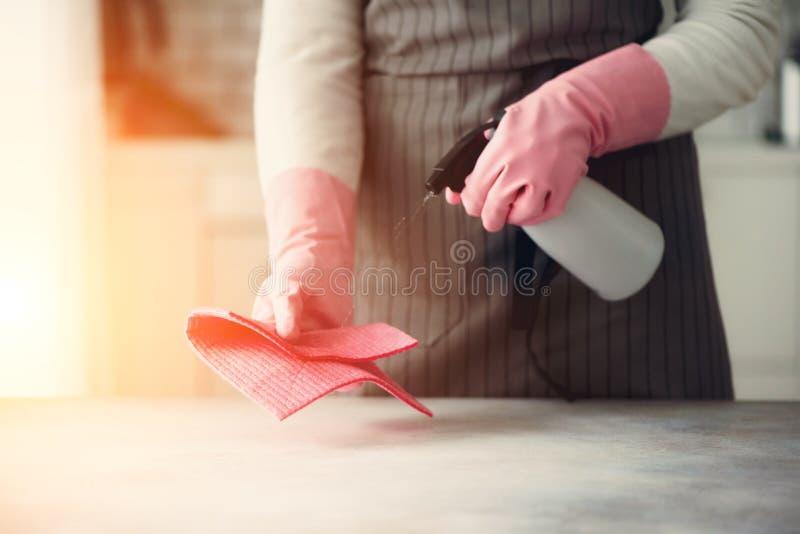Kvinnan i gula rubber skyddande handskar som torkar damm och, smutsar ner Lokalvårdbegrepp, baner, kopieringsutrymme fotografering för bildbyråer