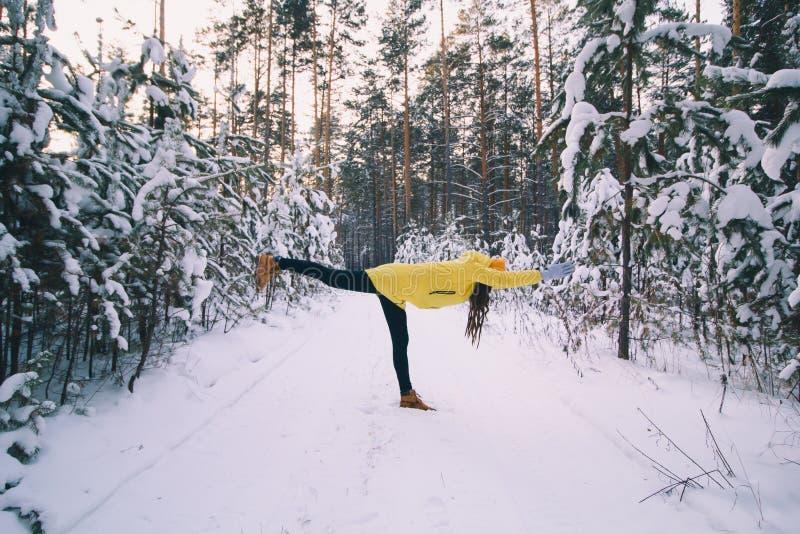 kvinnan i gult omslag och hatten som gör genomkörare eller yoga i vinter, parkerar fotografering för bildbyråer