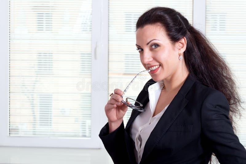 Kvinnan i håll för affärsdräkt fjättrar exponeringsglas i munnen arkivbild