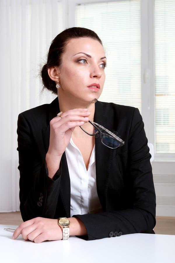 Kvinnan i håll för affärsdräkt fjättrar exponeringsglas i munnen och tuen royaltyfria foton