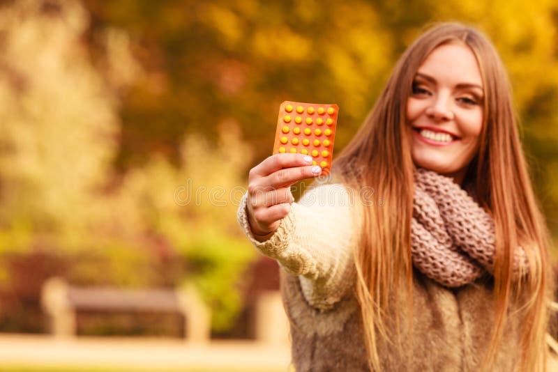 Kvinnan i höst parkerar hållande vitaminmediciner fotografering för bildbyråer