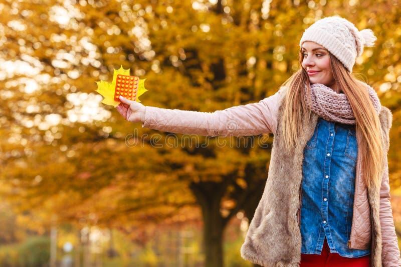 Kvinnan i höst parkerar hållande vitaminmediciner arkivfoto