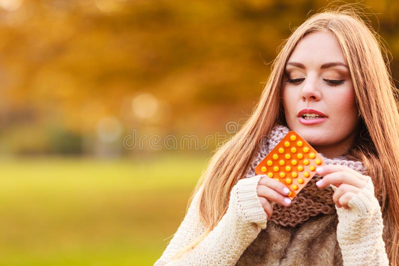 Kvinnan i höst parkerar hållande vitaminmediciner royaltyfri bild