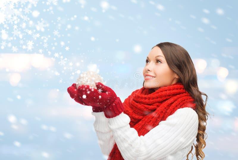 Kvinnan i halsduk och tumvanten med jul klumpa ihop sig arkivfoto