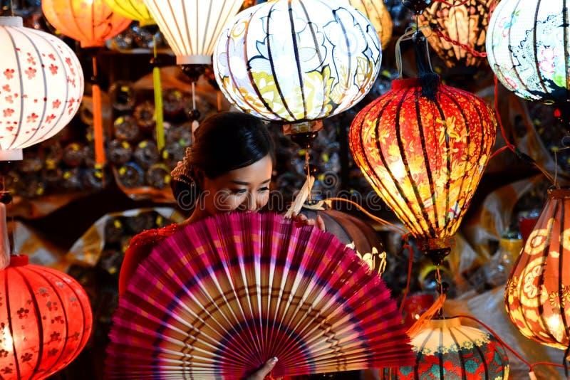 Kvinnan i handcrafted lyktor shoppar Peka av interst i Vietnam vietnam royaltyfri foto