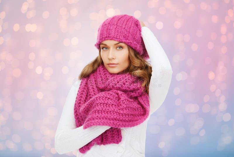 Kvinnan i hatt och halsduk över rosa färger tänder bakgrund arkivfoto