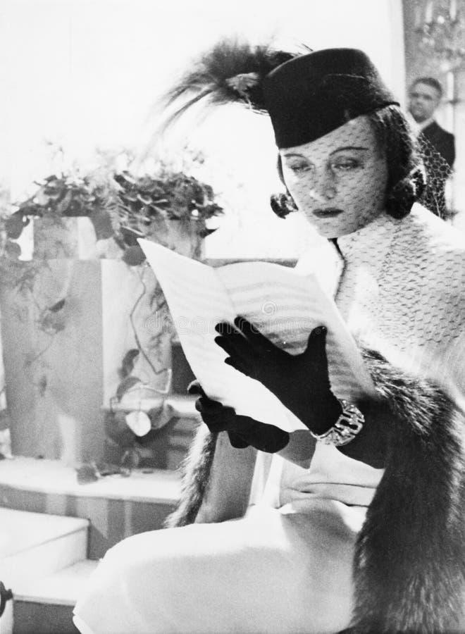 Kvinnan i hatt och skyler läs- notblad (alla visade personer inte är längre uppehälle, och inget gods finns Leverantörgarantier t royaltyfri fotografi