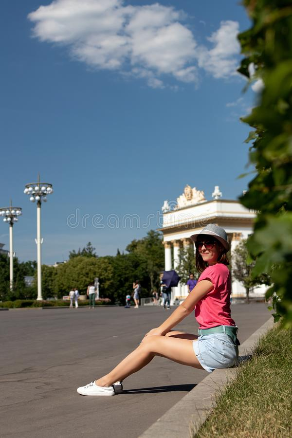 Kvinnan i hatten som sitter på gränsen i, parkerar, Moskva royaltyfri bild