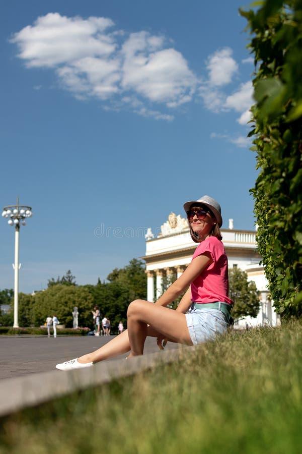 Kvinnan i hatten som sitter på gränsen i, parkerar, Moskva royaltyfria foton