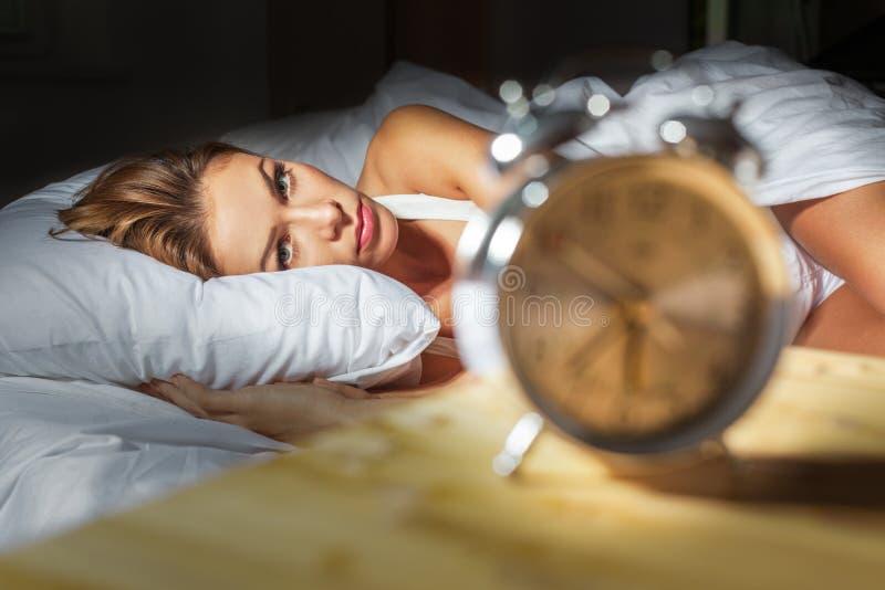 Kvinnan i hennes säng med sömnlöshet och mardrömmar kan arkivfoto