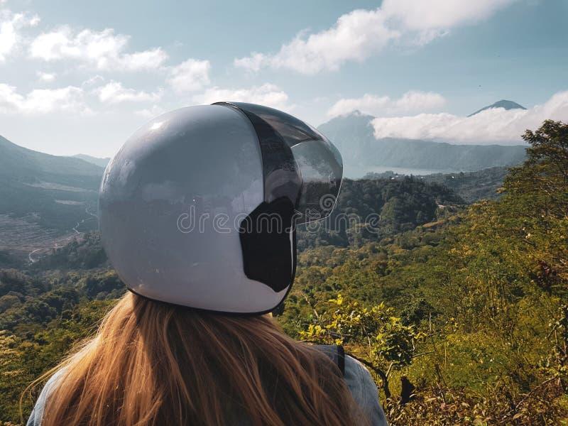Kvinnan i hjälm beundrar härlig bergsikt i Bali royaltyfri foto