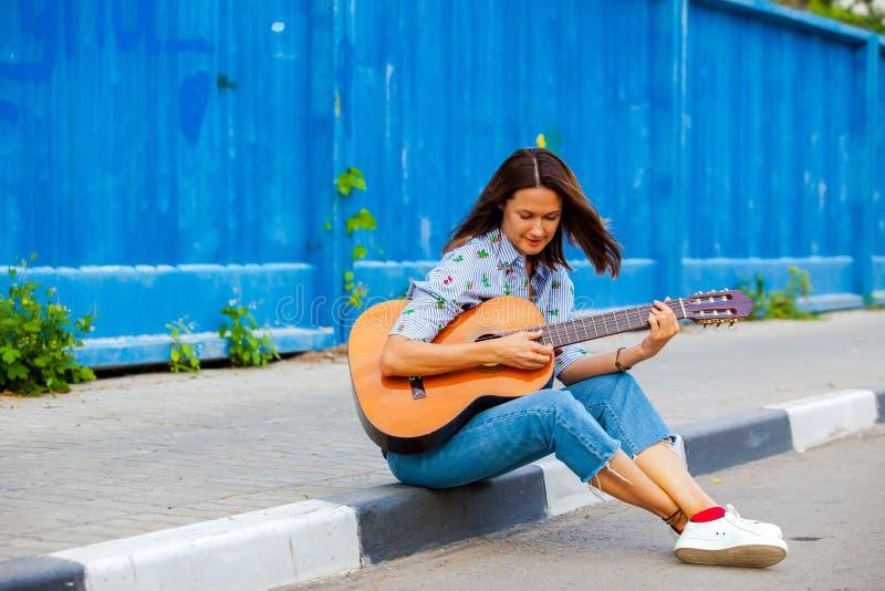 Kvinnan i jeans sitter på en vägtrottoarkant och spelar gitarren royaltyfri foto