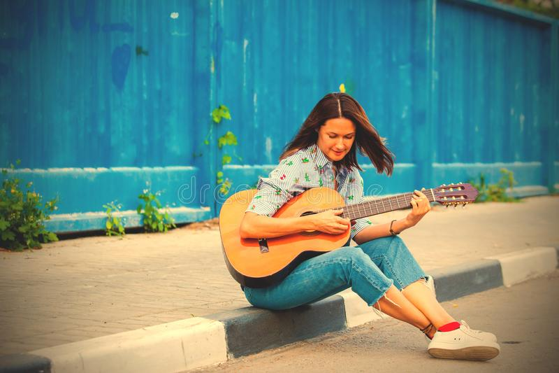 Kvinnan i jeans sitter p? en v?gtrottoarkant och spelar gitarren arkivbild