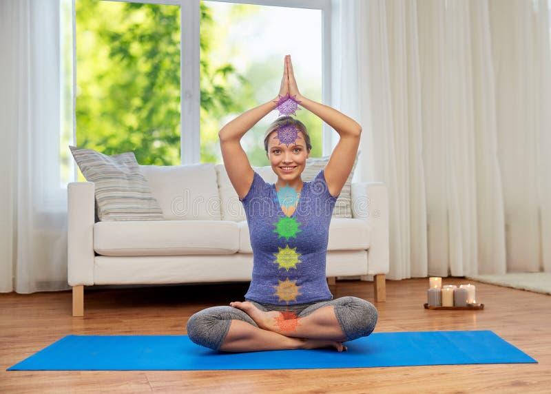 Kvinnan i lotusblomma poserar att g?ra yoga med sju chakras arkivfoto