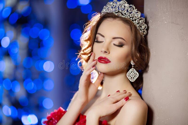 Kvinnan i luxklänning med kronan som drottning, prinsessan, ljus festar royaltyfri bild