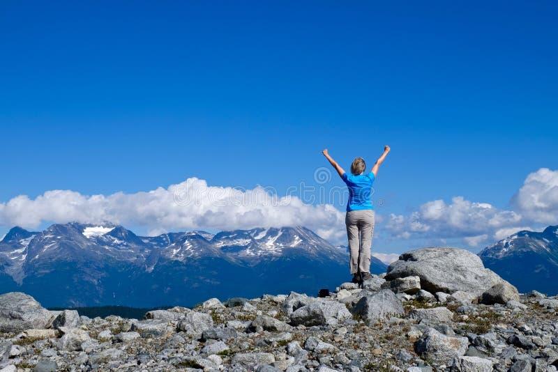 Kvinnan i lyckat poserar på bergöverkant royaltyfria foton