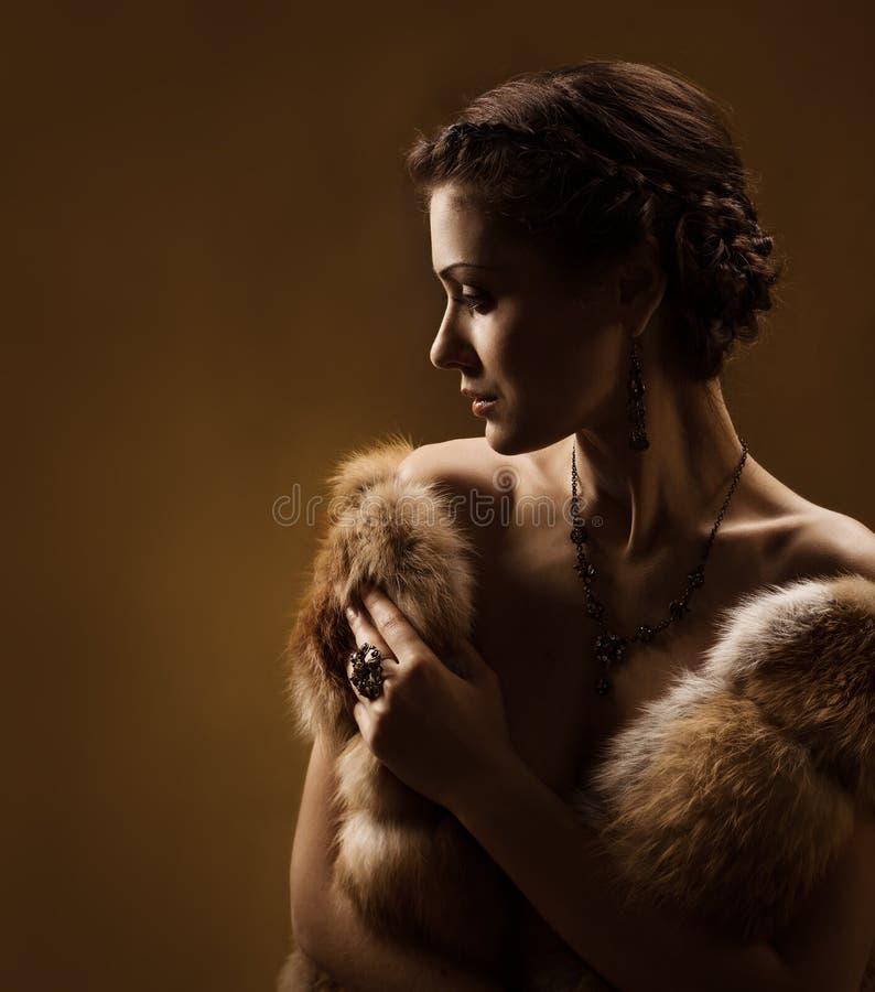 Kvinnan i lyx pälsfodrar täcker. Tappning utformar.   arkivbild