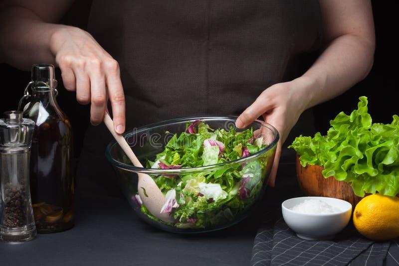 Kvinnan i processen av danandegrönsaksallad äta som är sunt begreppet bantar En sund livsföring Kock hemma arkivbilder