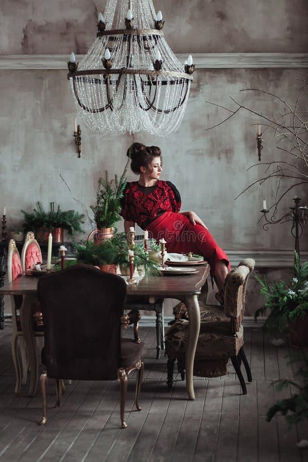 Kvinnan i röd tappningklänning sitter på tabellen som tjänas som för julmatställe Vindinre med den klara betongväggen arkivbild