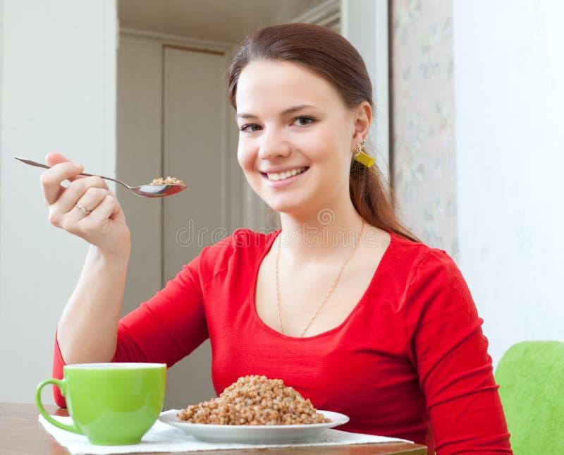 Kvinnan i rött äter bovetehavregröt royaltyfri fotografi