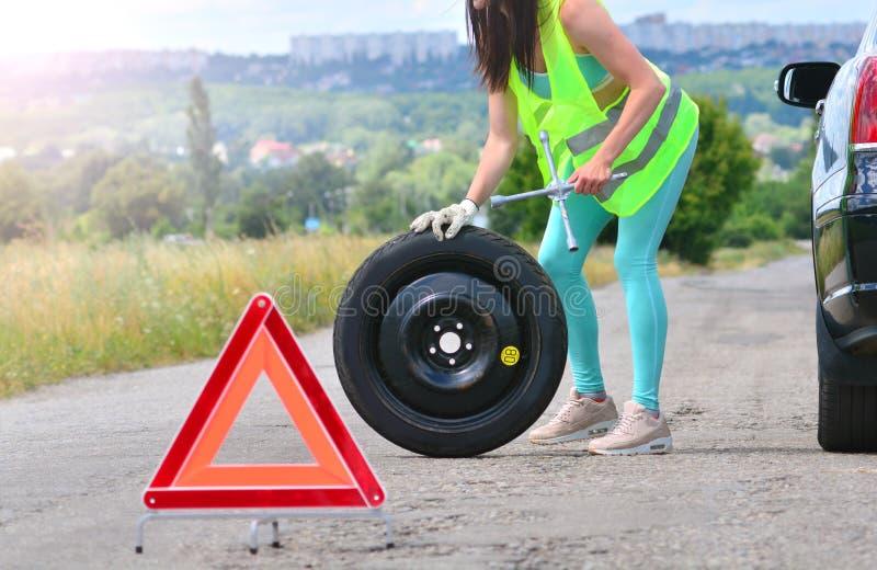Kvinnan i reflekterande väst rymmer hjulskiftnyckeln och rullar det extra- hjulet Utbyte för extra- hjul Stansat hjul på vägen me royaltyfria foton