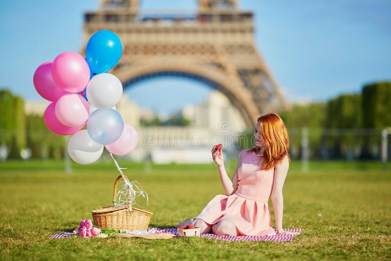 Kvinnan i rosa färger klär med gruppen av ballonger som har picknicken nära Eiffeltorn i Paris arkivbilder