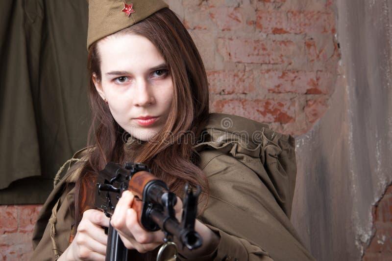 Kvinnan i rysk militär likformig skjuter ett gevär Kvinnlig soldat under det andra världskriget royaltyfri bild