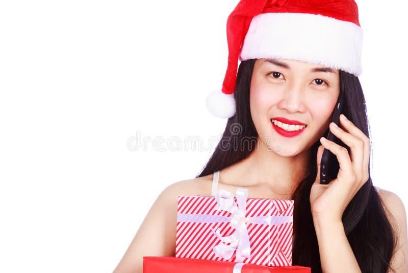 Kvinnan i Santa Claus beklär att kalla på mobiltelefonen med gåva b royaltyfria bilder