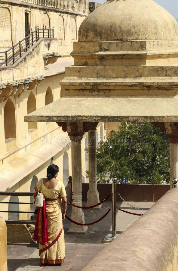 Kvinnan i sari står på balkongen Amber Fort i Jaipur, Rajasthan, Indien royaltyfri foto