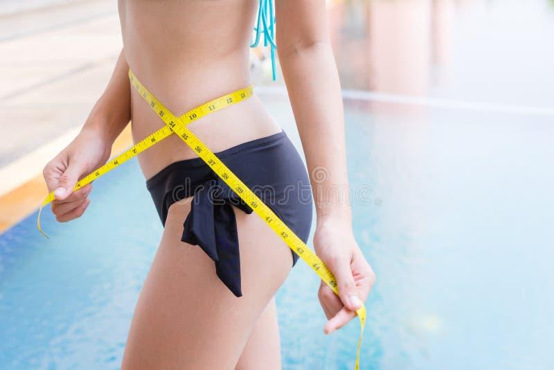 Kvinnan i sexig bikini med den slanka kroppen som mäter låret med mätningstyp efter, bantar med simbassängen i bakgrund royaltyfria foton