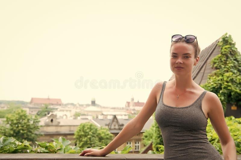Kvinnan i sexigt tilldelar krakow, Polen Sinnlig kvinnaställning på cityscape på vit himmel Reslustaffärsföretaget och upptäcker royaltyfria bilder