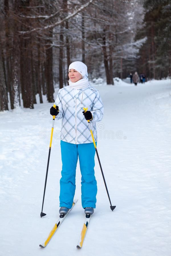 Kvinnan i skida-kläder med skidar poler som står i vintrig skog royaltyfri foto