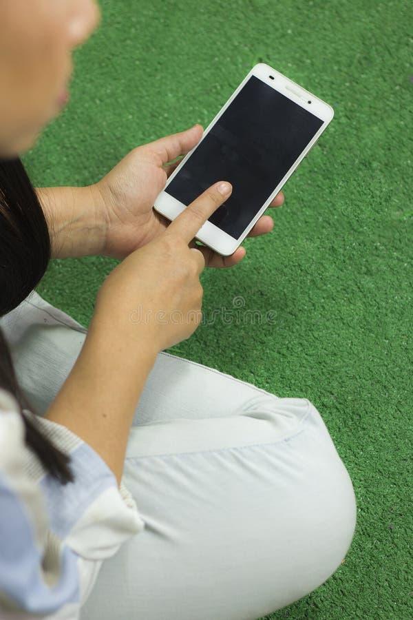 Kvinnan i skjortan som spelar p? telefonen som sitter p? ett gr?nt golv med ben, korsade royaltyfri bild