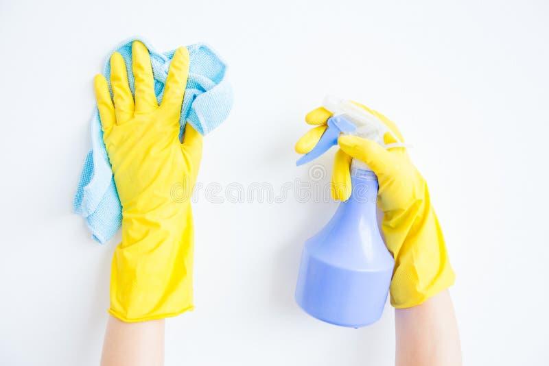 Kvinnan i skyddande handskar är le och torka damm genom att använda en sprej och en dammtrasa arkivbilder