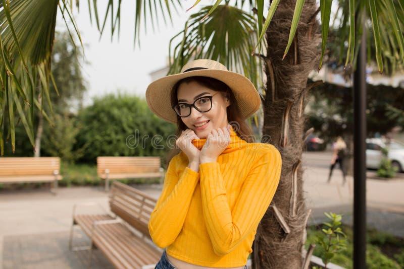 Kvinnan i staden har gyckel som skrattar Palmtr?d i bakgrunden Ljus gul kläder, exponeringsglas, hatt Sommargata royaltyfri bild
