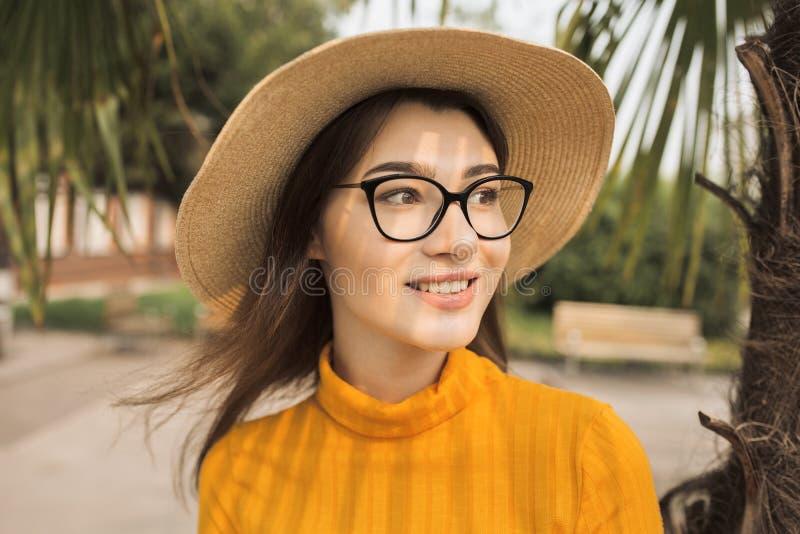 Kvinnan i staden har gyckel som skrattar Palmtr?d i bakgrunden Ljus gul kläder, exponeringsglas, hatt royaltyfria foton