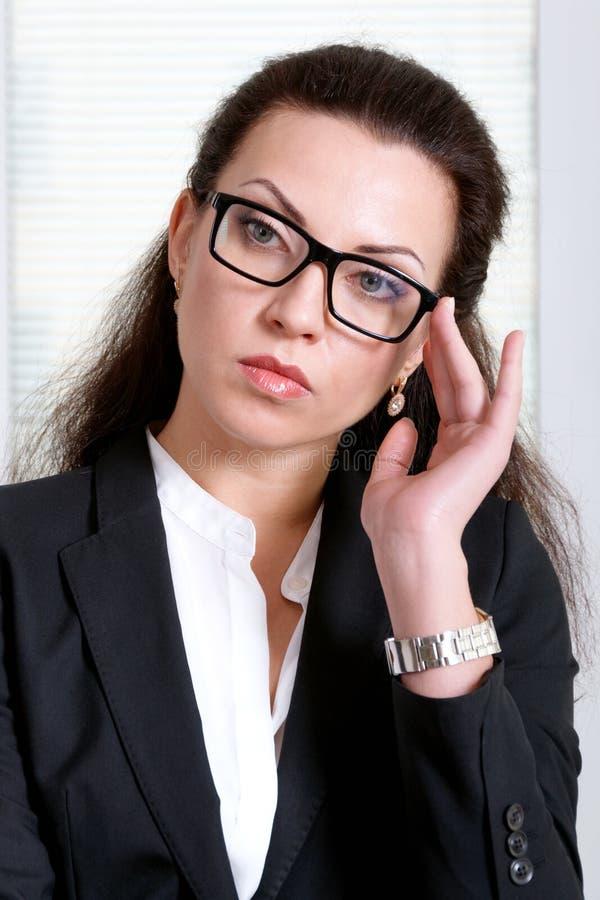 Kvinnan i svart affärsdräkt rymmer exponeringsglas på hennes framsida royaltyfri fotografi