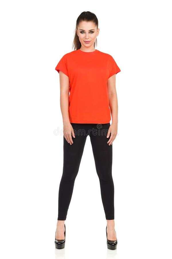 Kvinnan i svart damasker och den Oragne skjortan står ben ifrån varandra royaltyfri fotografi