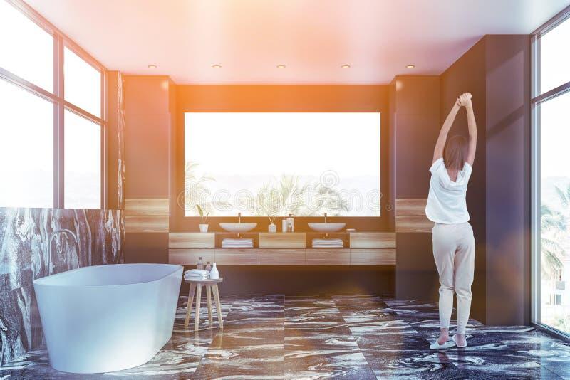 Kvinnan i svart marmorerar badrummet arkivbild