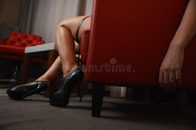 Kvinnan i svart skor att sova i röd läderstol arkivbilder