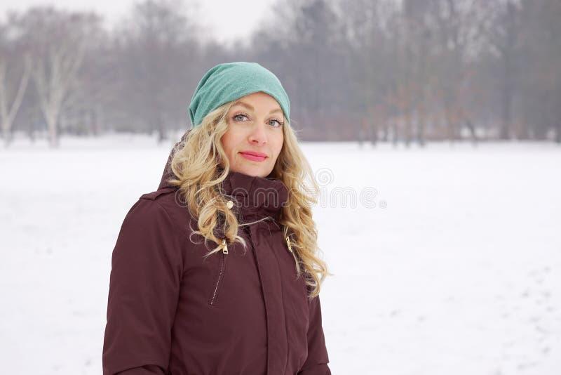 Kvinnan i täckt snö parkerar i vinter arkivfoto