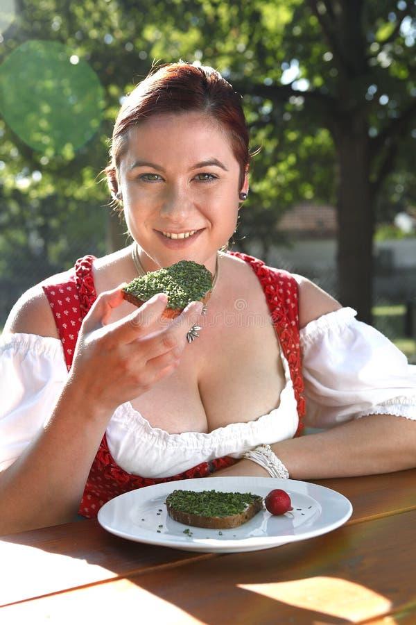 Kvinnan i typisk bayersk dräkt äter bröd med gräslökar i lodisar arkivfoto