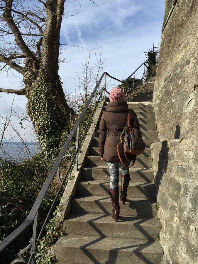 Kvinnan i vinterkläder går uppför trappan arkivfoton