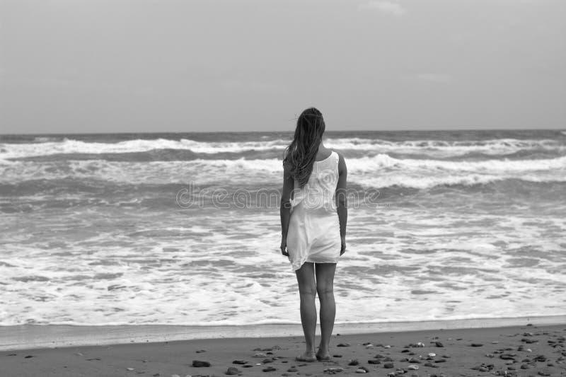 Kvinnan i vit underplagg som ser havet arkivfoton