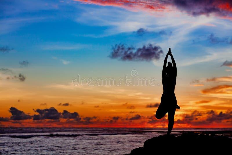Kvinnan i yoga poserar på havsstranden vaggar fotografering för bildbyråer