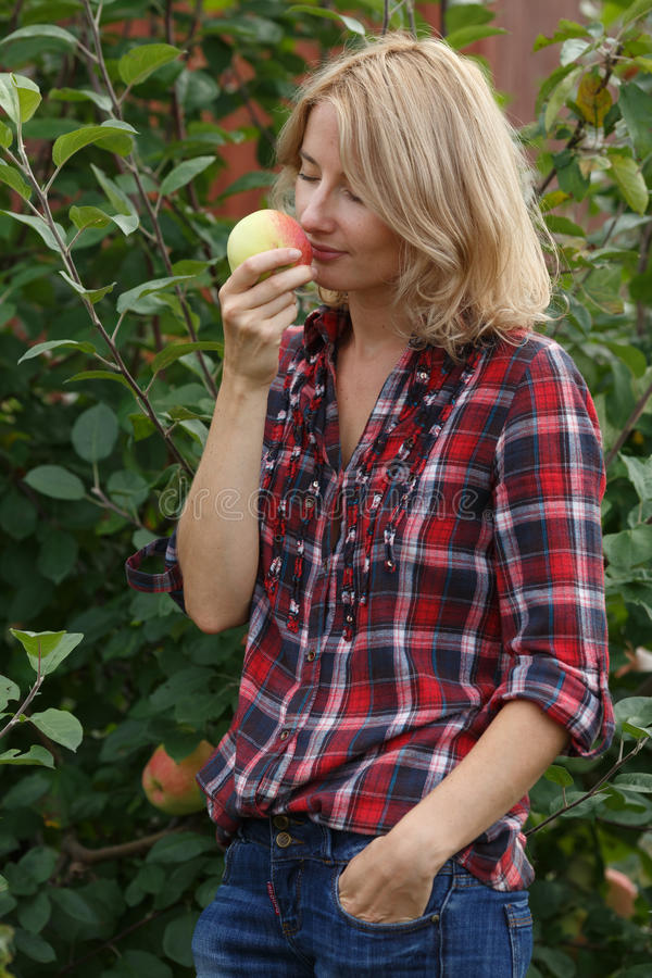 Kvinnan inhalerar arom av ett äpple arkivfoto