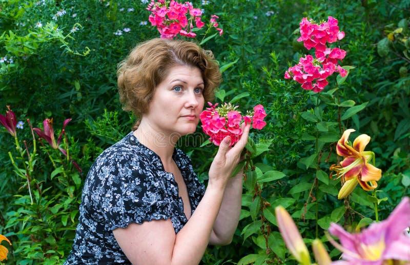 Kvinnan inhalerar arom av floxen i trädgård arkivbild