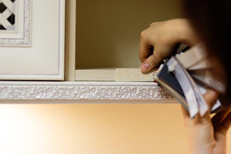 Kvinnan jämför och mäter genom att använda den färgrika texturmodellen och färgpaletten - provkartor som ska väljas från arkivbild