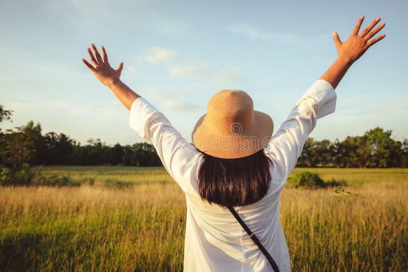 Kvinnan känner sig fri i fältet arkivfoto